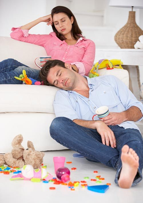 Exhausted parents on the sofa