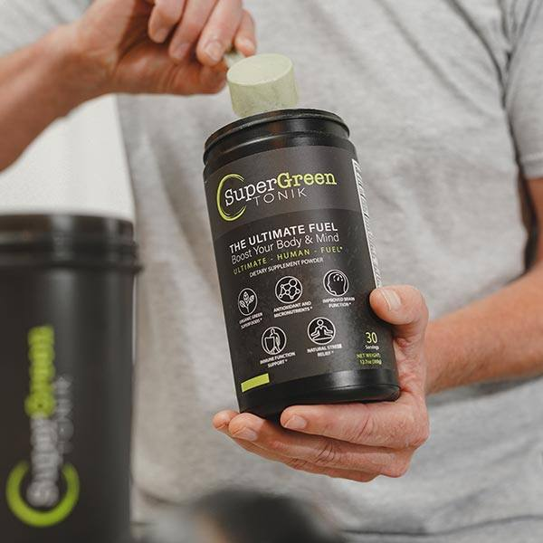 Guy scooping SuperGreen TONIK from tub to shaker