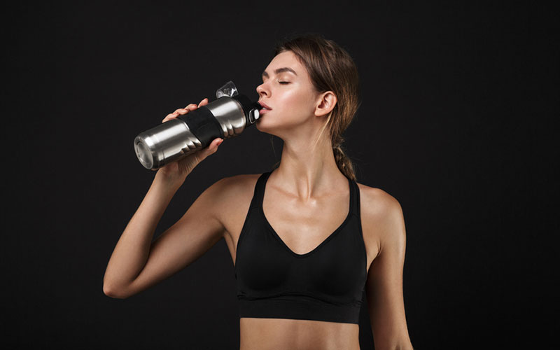 Exercising woman drinking